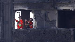 firemen search burnt out shell of Grenfell Tower