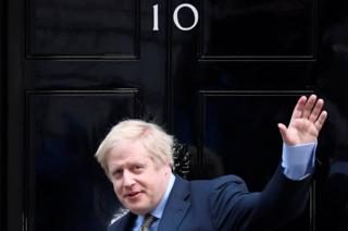 Boris Johnson waves as he arrives at Downing Street