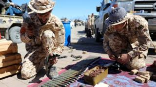 Members of Misrata forces sort through ammunition