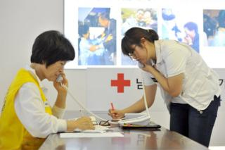 In this file photo taken on 22 August 2013, South Korean Red Cross officials talk on phones as they receive applications for an expected inter-Korean family reunion programme at the Red Cross office in Seoul
