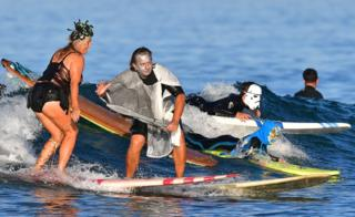 Surfers at the 16th Annual Blackies Halloween Surf event