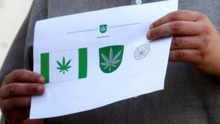 Designer Tonu Kukk holds a paper with a design of Kanepi municipality's flag