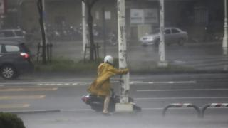 A motorist holds on to a post as she braves high winds and rain of Super Typhoon Meranti in Kaohsiung, southern Taiwan, 14 September 2016.