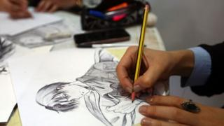 An artist draws an illustration at a stall during the Libya Comic Convention, in the capital Tripoli (02 November 2017)