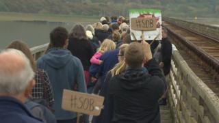 Campaigners held Save Our Bridge banners as they made their way across the estuary