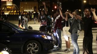 Group of protestors stand in fron of car holding hands in response to police shootings of African-Americans in USA