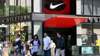 Pedestrians walk by a NikeTown store in San Francisco, California