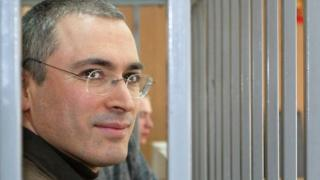 Former CEO of Russian oil gaint Yukos Mikhail Khodorkovsky smiles from behind bars, as he listens to a prosecutor during his trial in Moscow, Monday, March 28, 2005.