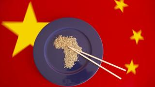 A plate with rice in the shape of Africa with the Chinese flag in the background