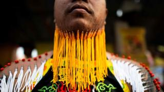 A devotee of the Loem Hu Thai Su shrine waits to parade with needles pierced through his chin