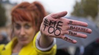 """一名参与""""#我也是""""(#metoo)的女性展示手中的涂鸦"""