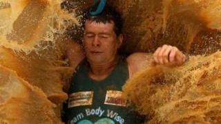 Un empleado cayendo en un enorme charco de agua enlodada