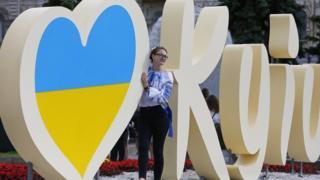 Дівчина фотографується біля знаку I Love Kyiv