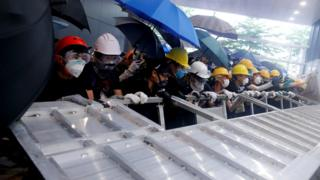 Protesters use a barricade to smash into the Legislative council building