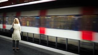 Women stand near train wey dey move