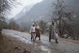 A Kashmiri family walks towards a vehicle as they leave home