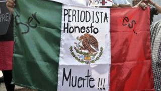 "A woman holds Mexican flag with an inscription that reads ""To Be a Honest Journalist is Death"" during a demonstration on 1 August, 2015,"
