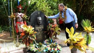 Mr Abbott places his hand on the headstone of Eddie Mabo