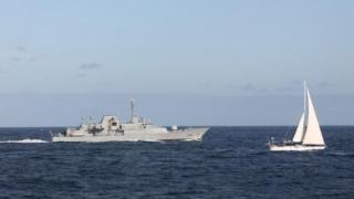 The Irish naval vessel - the LÉ Niamh, sails alongside the detained yacht Makayabella