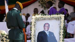 A soldier stands beside a picture of former Zimbabwean President Robert Mugabe during a church service at his rural village in Kutama, Zimbabwe, September 28, 2019