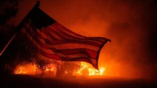 A US flag is seen in the blaze