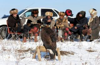 Participants gather during a traditional hunting contest with tamed golden eagles and hawks