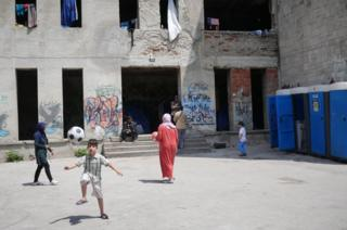 A young boy plays with a ball in front of the building, which has no doors or windows - a few portable toilets stand against a nearby wall
