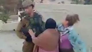 Screengrab of a video showing a Palestinian girl appear to strike an Israeli soldier in the West Bank village of Nabi Salih on 15 December 2017