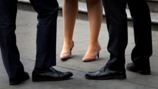 Stock image of men and a woman standing together