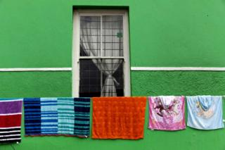 Washing hangs from a line outside a house that is painted green.