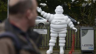 A Michelin employee walks past a life-size model of the company's mascot outside its Ballymena factory