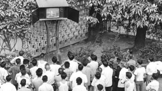 In a park, viewers gather around to watch the television broadcast of the Apollo 11 moon landing, Hong Kong, July 1969