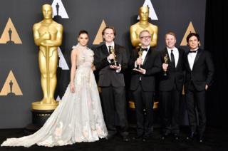"""Команда """"Зоотрополіса"""" - переможці у номінації за найкращий анімаційний фільм - позують із нагородами за лаштунками церемонії."""
