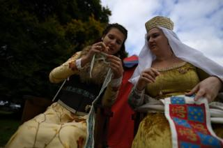 Two women dressed in medieval costume sew together