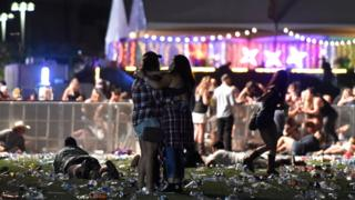 people hugging during Las Vegas attack, others ducked and fleeing