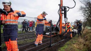 Workers in orange uniforms assemble the first portions of a metal fence on the Danish border, while camera crews look on nearby
