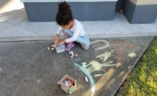 Girl drawing outside the MMC church