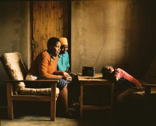 Solonge with her bother and brother listen to a read in their home