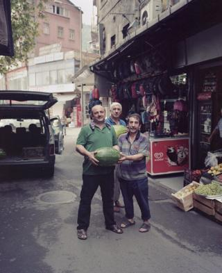 Three men stand with a melon