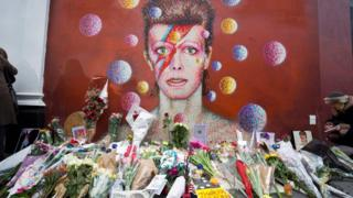 Flowers start to mount up by David Bowie mural in Brixton