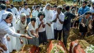 Mujeres llorando ante tumbas