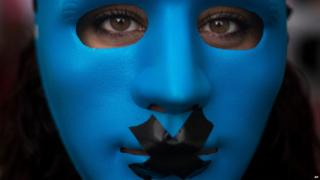 A protestor wears a mask with a gag as she marches against the Public Security Law in Madrid, Spain, Tuesday, June 30, 2015.