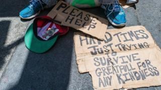 A homeless person begging for money with signs saying
