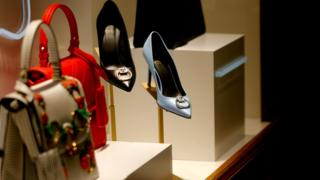 Women's luxury bags and heeled shoes, manufactured by Versace, sit on display at the GUM department store on Red Square, in Moscow, Russia on October 31, 2018.