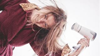 Una mujer secándose el pelo