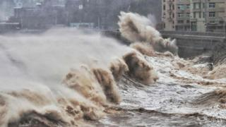 Waves hit a sea wall in front of buildings in Taizhou, China's eastern Zhejiang province on August 9, 2019.