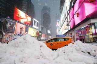 A taxi drives past piles of snow as a storm sweeps through Times Square in New York on 14 March 2017.