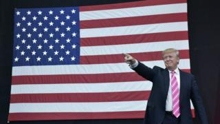 Donald Trump points in front of an American flag