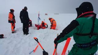 A group of men in bright orange clothes digging into the snow.