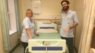 Nursing staff standing either side of a new hospital bed